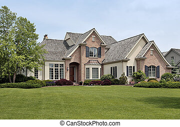 Large luxury brick home in suburban setting