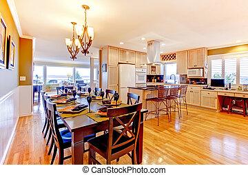 Large luxury dining room and kitchen witj shiny wood floor.