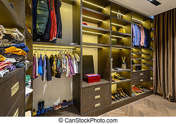 Large luxury men's wardrobe with different clothes shoes and...