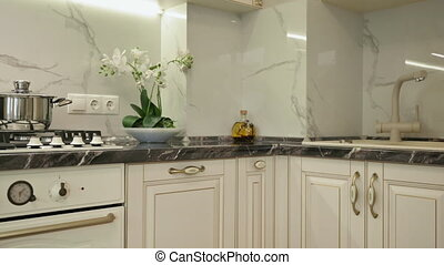 Panorama shot of large luxury trendy beige moden classic kitchen