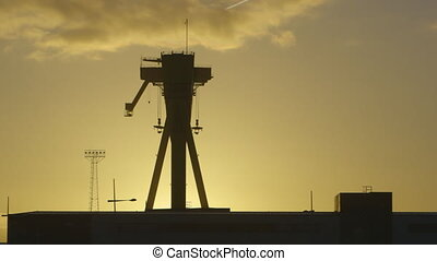 Large Machinery Silhouette - Steady, exterior, wide shot of...