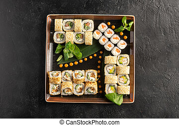 Large maki sushi set with a varied assortment of Japanese rolls in a square plate on a black stone table.