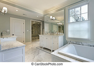 Large master bath in luxury home with white cabinetry