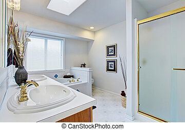 Large master bathroom with light blue walls.
