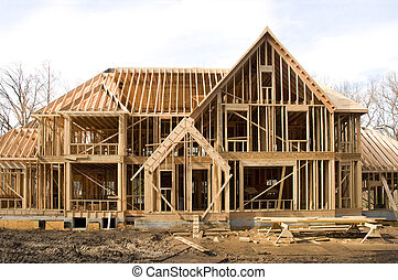 McMansion type house under construction in framing phase -...
