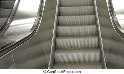 Large modern staircase escalator rides the subway up and...