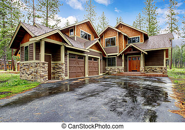 Large mountain cabin house with stone and wet driveway. -...