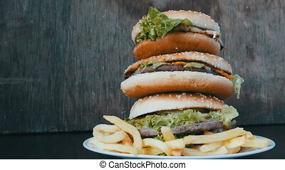 Large mountain of three burgers on a plate with French...