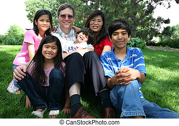 Large multiracial family sitting on lawn