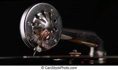 Large needle of a vintage gramophone on rotates vinyl record. Vintage musical instrument on a black studio background. Nostalgia. Retro turntable close up. Detailed macro shooting. Slow motion