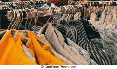 Large number of multi-colored warm winter sweaters hang on ...