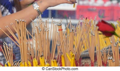 Large number of yellow sticks of good luck smoke in front of...