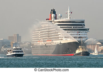 ocean liner - large ocean liner being escorted from port by...