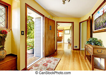Large old luxury house entrance with art and yellow walls. -...