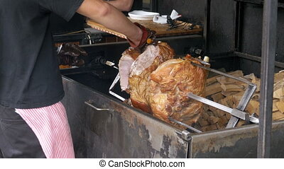 Large Piece meat Roast Pork Leg prepared on a Spit above an...