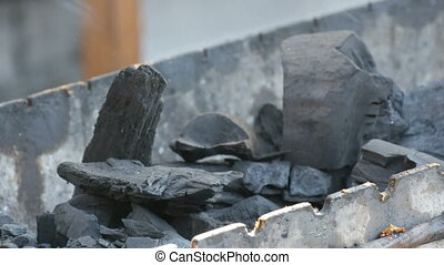 Large pieces of smoking coals lie on the grill - Large...