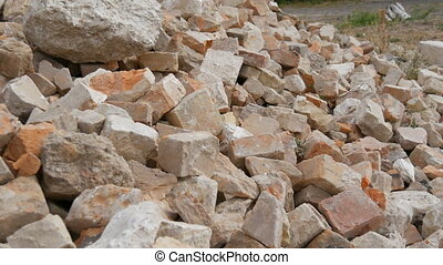 Large pile of building bricks or the remains of a destroyed building in a heap at a construction site