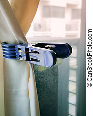 Large plastic cloth clip can be temporarily attached to the curtain. Close up and selective focus.