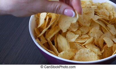Large plate with potato chips on the table. Female hands...
