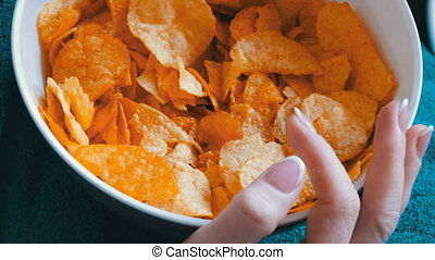 Large plate with potato chips. The woman lies on the couch...