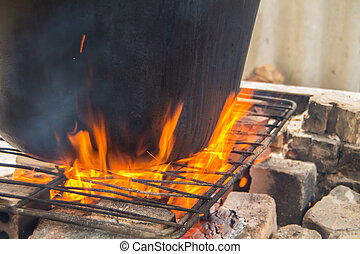 Large pot is on a fire - Large pot in which cooked food is...