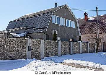 private house behind a stone fence near the road in the snow