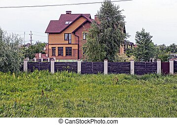 large private house with windows behind a wooden fence with a gate in the green vegetation on the street
