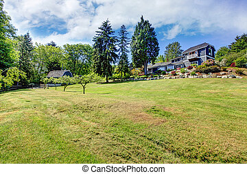 Large property with blue house and trees.