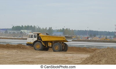 Large quarry dump truck rides, driving on construction site....