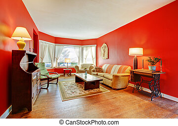 Large red living room with hardwood and antique furniture. -...