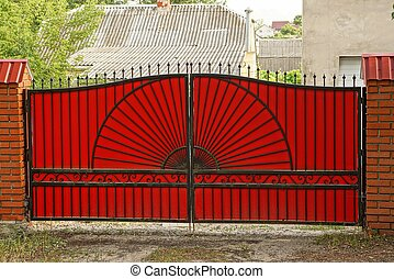 large red metal gates on a brick fence in the street