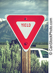 Large red yield sign in a countryside