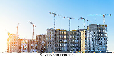 Large residential complex real estate apartments, under construction with high cranes. Panorama view