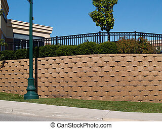 Large retaining wall with a black wrought iron fence behind bushes running along the top.