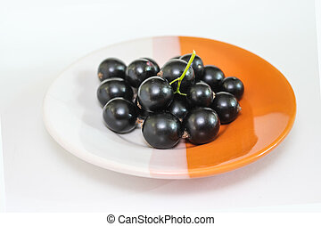 Large ripe berries of a black currant on a plate