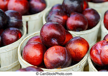 Large ripe plum fruits sold in the market.
