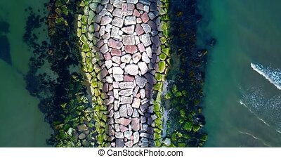 Large rock mass forms artificial mole from beach to boundless sea in Venetian lagoon at bright sunlight in spring aerial view