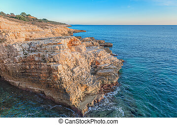 Large rocky coastline under blue sky