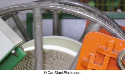 Rubber tape is reeled up on a drum in the machine.