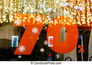 Large Sale 70% discount, a banner on the glass with the reflection of New Year's garlands