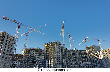 Large-scale construction of a residential complex with a view of construction cranes