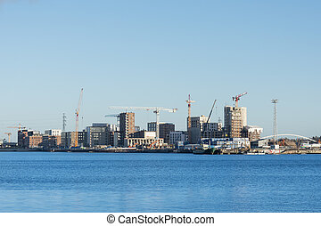 Large-scale construction with cranes on the bay coast of the city.
