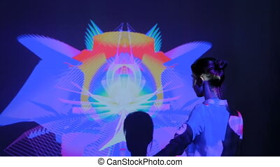 Large screen augmented reality experience - woman waving arms in front of interactive display with multi color projector light at modern futuristic immersive exhibition. AR and technology concept