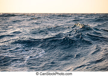 Large sea waves at sunset closeup