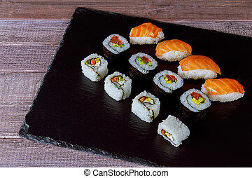 Large set of japanese rolls on a black plate