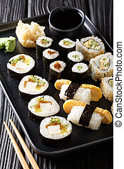 large set of Japanese rolls such as Hosomaki, Uramaki, Maki, Nigiri, Tamagoyaki served with ginger, wasabi and soy sauce close-up on a plate. vertical