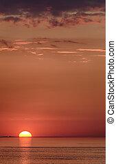 setting sun - large setting sun on the horizon at sea