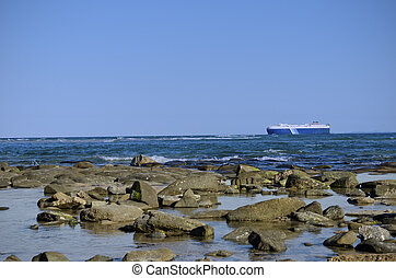 Large ship close to rocky shore