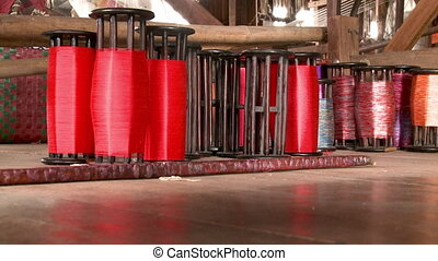 Large spools with red threads for use in the loom