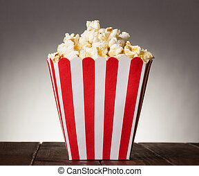 Large square box filled with top popcorn on gray background....